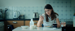Girl with iPhone at breakfast table
